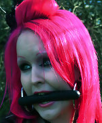 Sexy pink haired woman tied and gagged outdoors